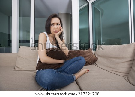Full length of tensed young woman holding cushion on sofa in living room - stock photo