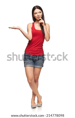 Full length of thinking beautiful woman showing holding on the palm blank copy space over white background - stock photo