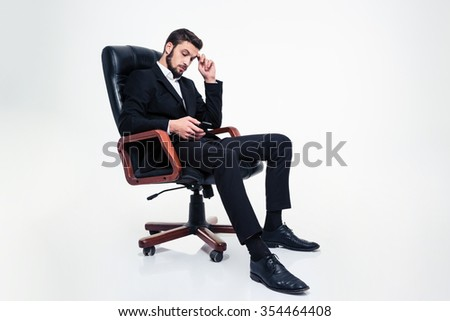 Full length of thoughtful attractive bearded businessman in black suit and shoes sitting in black leather office chair and using mobile phone over white background - stock photo