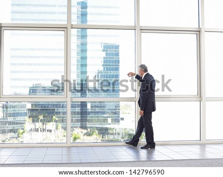 Full length of thoughtful businessman standing by glass window in office building