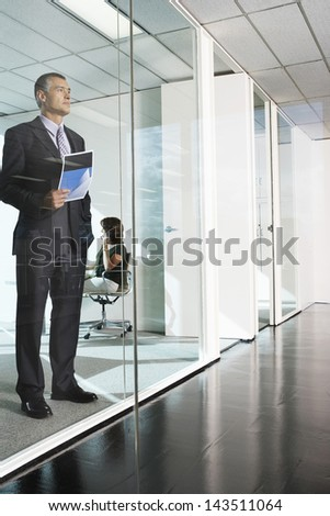 Full length of thoughtful middle aged businessman standing against glass wall in office - stock photo
