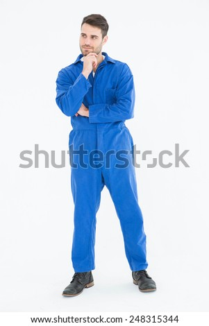 Full length of thoughtful young male mechanic with hand on chin on white background - stock photo