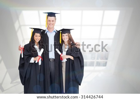 Full length of three friends graduate from college together against room with large window showing city