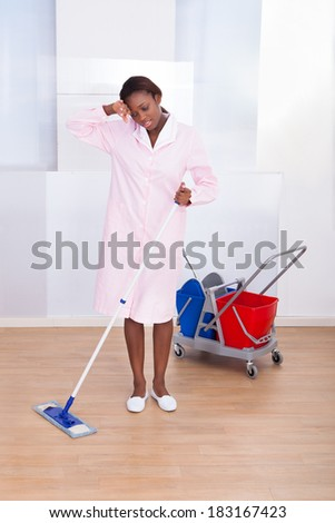 Full length of tired female housekeeper cleaning floor in hotel