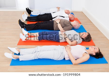 Full length of trainer and senior people lying on exercise mats at gym