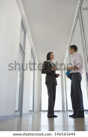 Full length of two business people discussing in office corridor - stock photo