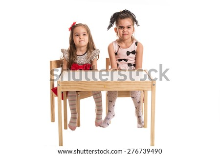 Full length of two girls sitting at table and make wry faces isolated on white  background - stock photo