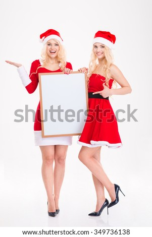 Full length of two happy beautiful sisters twins in red santa claus dresses and hats pointing on blank board and holding copyspace on palm over white background - stock photo