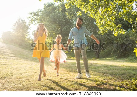 Full length of two happy parents with a healthy lifestyle wearing casual clothes while running together, with their cute daughter in a sunny day of summer