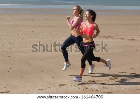 Full length of two healthy young women jogging on shore at beach - stock photo