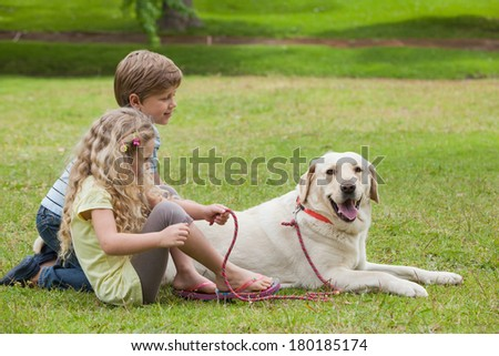 Full length of two kids with pet dog at the park