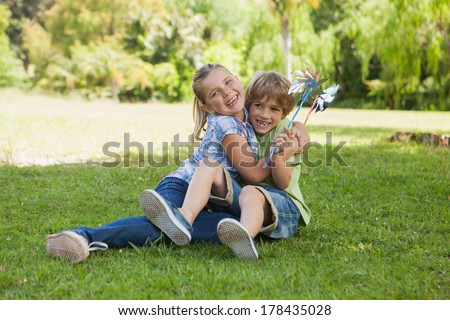 Full length of two kids with pinwheels playing at the park