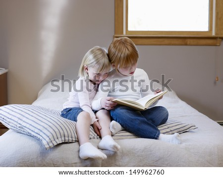 Full length of two young sisters reading book on a single bed - stock photo