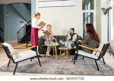 Full length of waitress presenting menu to female customer with friends in cafe - stock photo