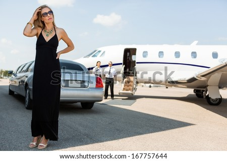 Full length of wealthy woman in elegant dress standing against limousine and private - stock photo