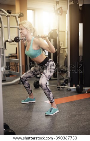 Full length of woman doing squat exercise - stock photo