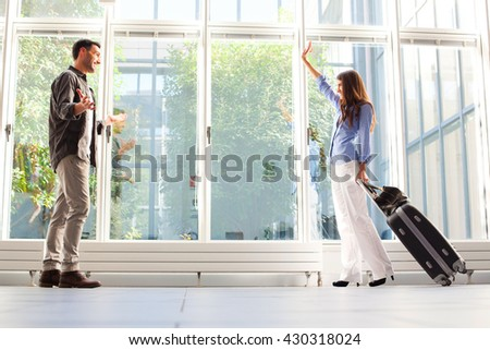 Full length of woman with luggage waving to her boyfriend. Young male and female partners are at airport. They are in casuals. - stock photo