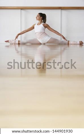 Full length of young ballerina doing split in rehearsal room - stock photo