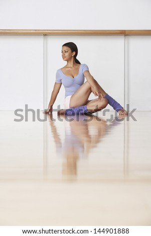 Full length of young ballerina practicing on wooden floor - stock photo