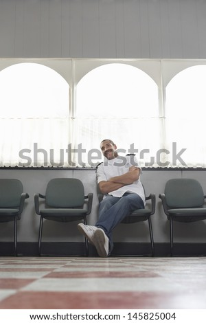 Full length of young barber sitting on chair in hair salon - stock photo