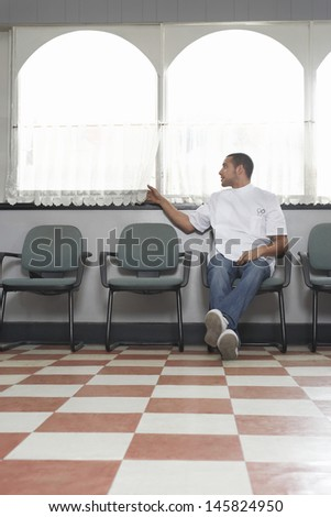 Full length of young barber waiting for customers in hair salon - stock photo