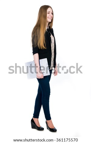 Full length of young blond smiling girl holding clipboard looking aside. Isolated on white background.