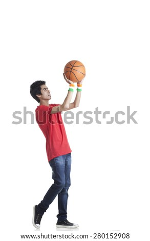 Full length of young boy in casuals aiming basketball over white background - stock photo