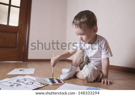 Full length of young boy painting with watercolors and paintbrush on floor - stock photo