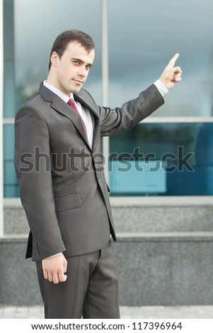 Full length of young business man in suit pointing at copy space on window