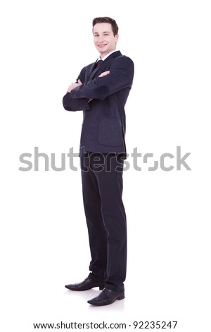 Full length of young business man standing with arms folded isolated on white background - stock photo