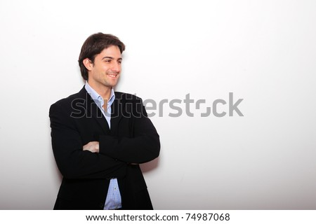 Full length of young business man standing with arms folded over light wall