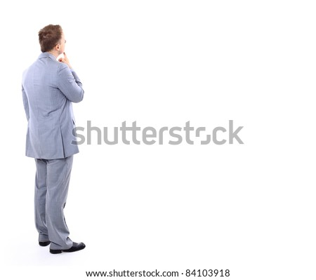 Full length of young business man standing with arms folded over light wall - stock photo