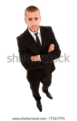 Full length of young business man standing with arms folded over white background - stock photo