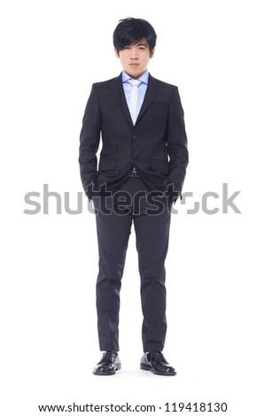 Full length of young business man standing with hands in pockets suit and smiling isolated