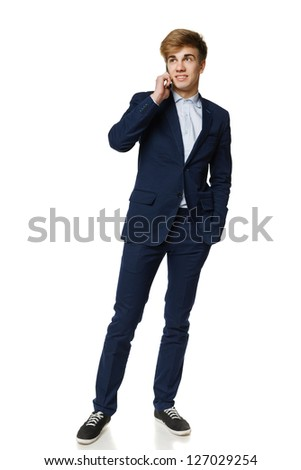 Full length of young business man talking on cellphone, over white background - stock photo