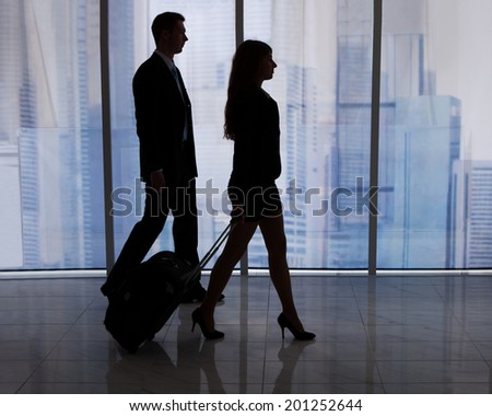 Full length of young businessman and businesswoman walking with luggage in office - stock photo