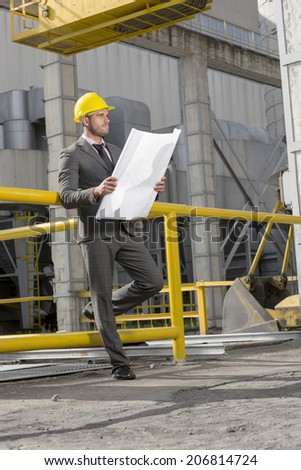 Full length of young businessman examining blueprint at construction site