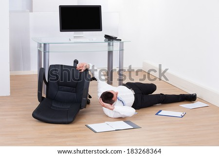 Full length of young businessman fallen from office chair - stock photo