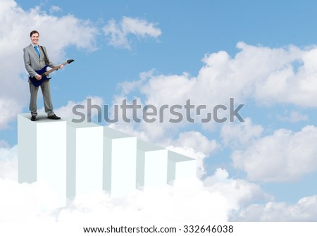 Full length of young businessman in suit standing on graph bars with guitar - stock photo