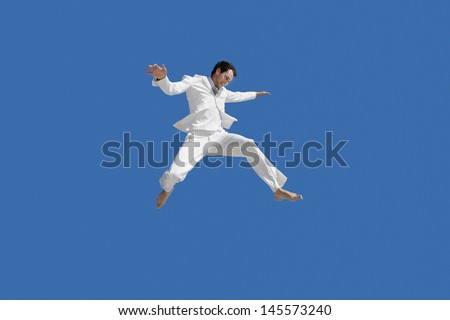 Full length of young businessman jumping against blue sky - stock photo
