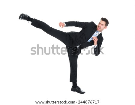 Full length of young businessman kicking over white background
