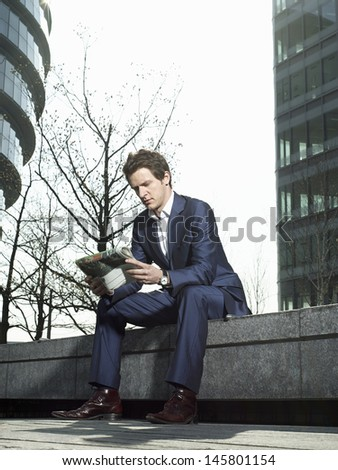 Full length of young businessman reading newspaper while sitting on wall outside office building - stock photo