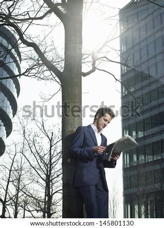 Full length of young businessman reading newspaper while standing under tree outside office building - stock photo