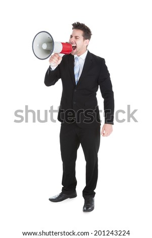 Full length of young businessman screaming into megaphone over white background
