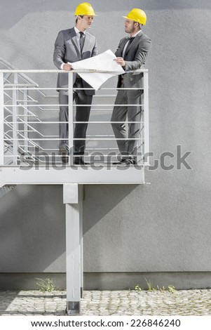 Full length of young businessmen discussing over blueprint on stairway - stock photo