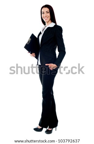 Full length of young businesswoman holding documents