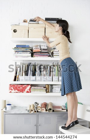 Full length of young businesswoman reaching for shelf in home office - stock photo