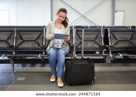 Full length of young businesswoman using digital tablet at airport lobby - stock photo