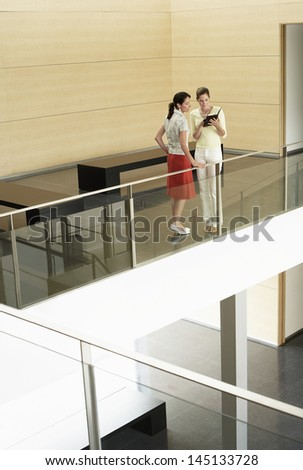 Full length of young businesswomen reading diary together while standing by glass railing in office - stock photo
