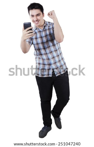 Full length of young casual man expressing happy after read good news on his smartphone - stock photo
